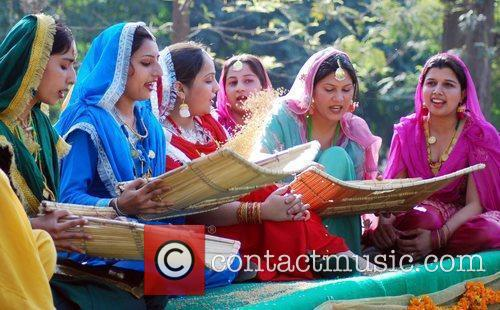 indian school girls sing folk songs as one of them winnows wheat in a ...