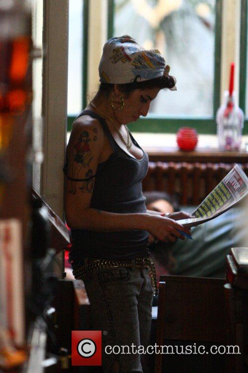 Amy Winehouse reads the paper whilst out with...