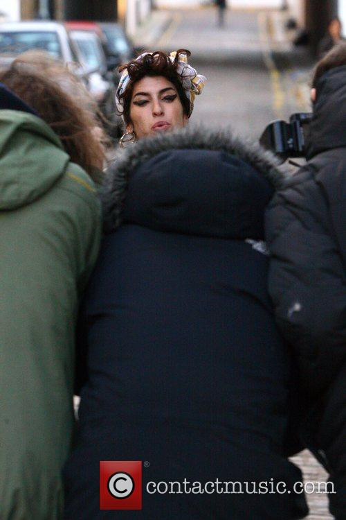 Amy Winehouse surrounded by paparazzi as she returns...