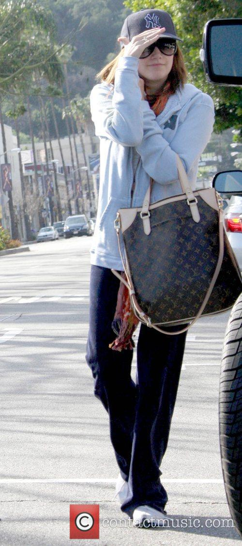 Ashley Tisdale covers her face while outside her...