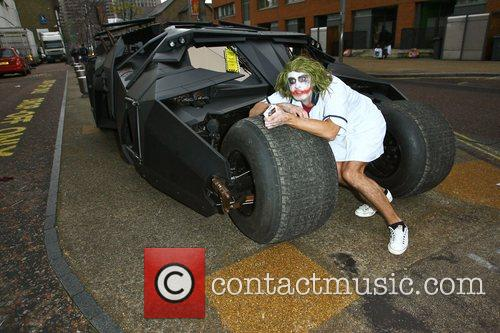 The Joker poses next to the Batmobile The...