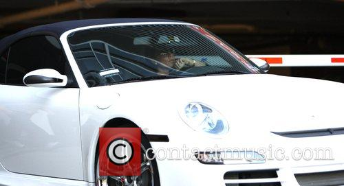 David and Victoria Beckham leave their office driving...