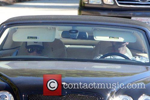 David Beckham and Victoria Beckham driving in their...