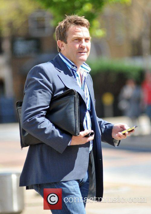 Checking his phone while leaving the ITV studios