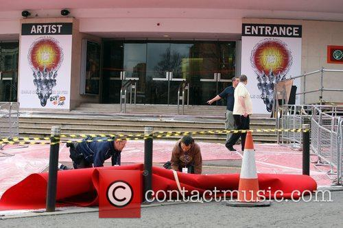 Workmen lay the red carpet and the final...