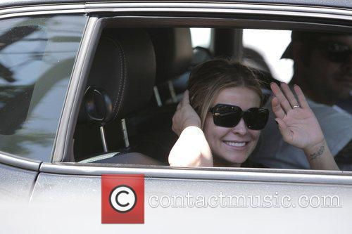 Carmen Electra waves and smiles at the camera...