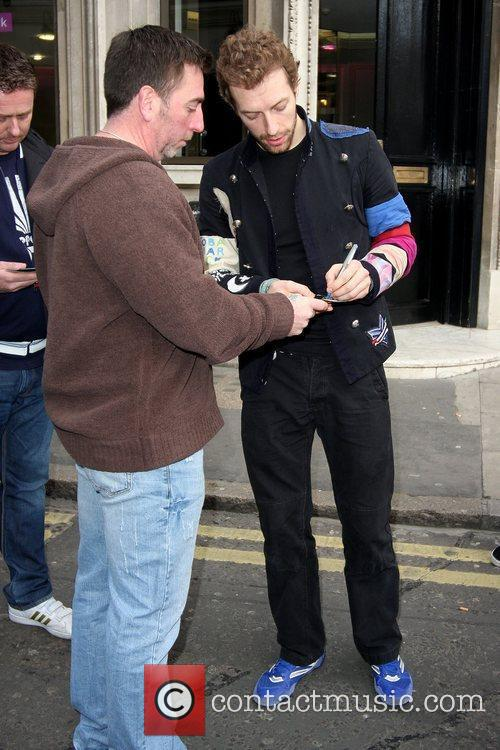 Chris Martin signs an autograph as he leaves...
