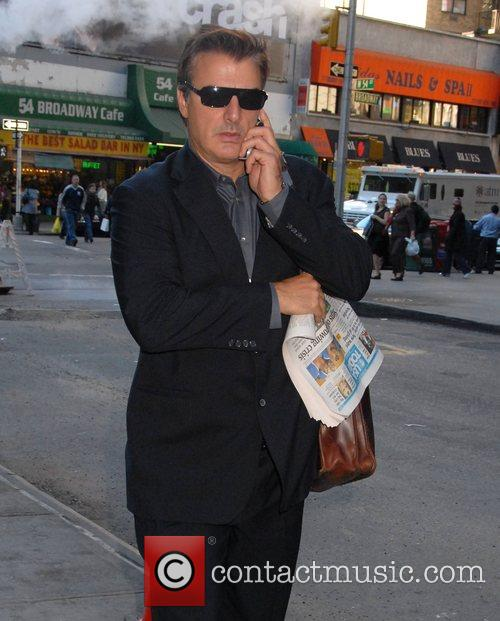 Chris Noth talks into his cellphone while out...