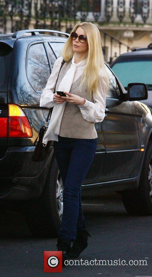 Claudia Schiffer checks her Blackberry while making her...