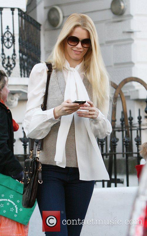 Claudia Schiffer smiles as she checks her Blackberry...