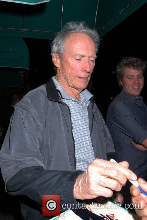 Clint Eastwood signs an autograph as he leaves...