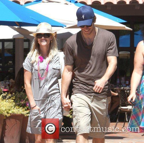 Reese Witherspoon and Jake Gyllenhaal holding hands while...