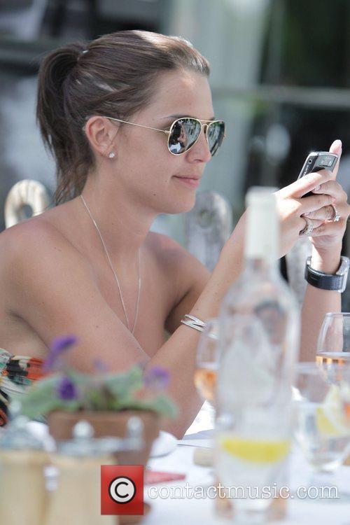 Danielle Lloyd texting on her Blackberry while having...