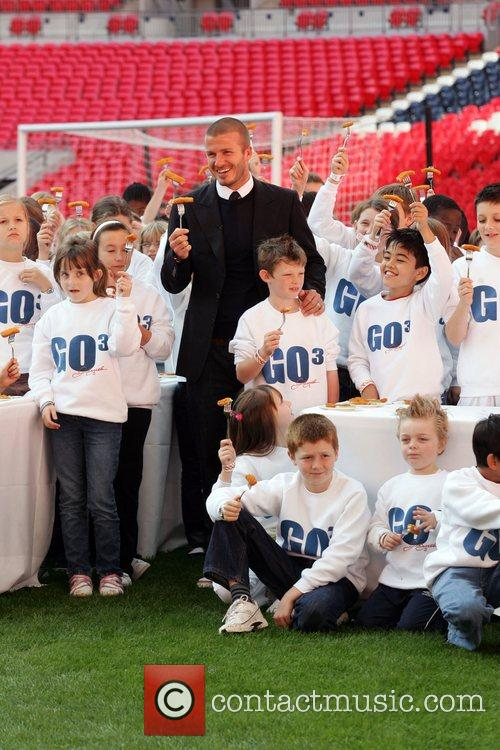 David Beckham  poses with children as he...