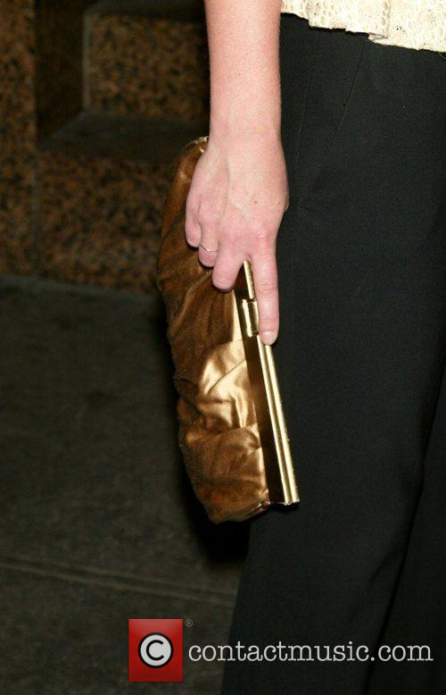 Julie Stiles shows off her purse at the...