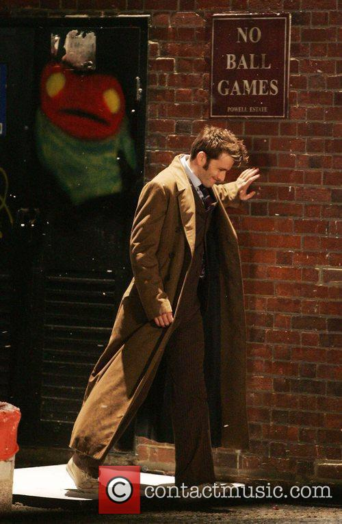 David Tennant looks in distress as he leans...