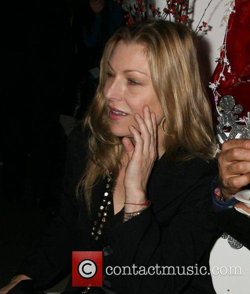 Tatum O'Neal wearing a red bracelet. A red...