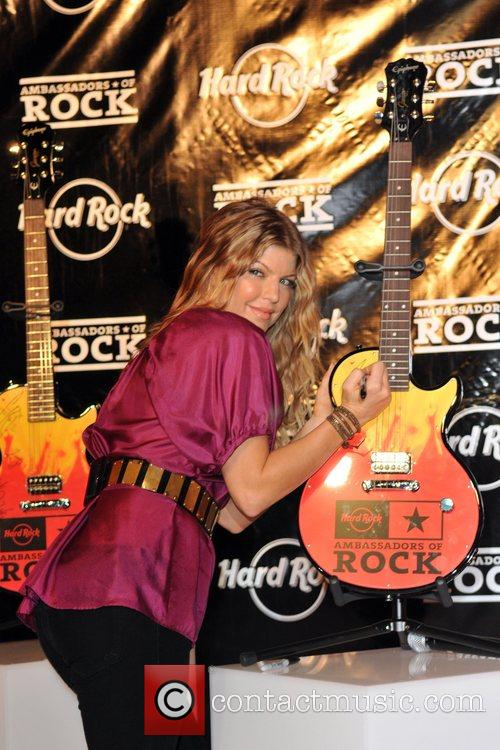 Autographs a guitar during an appearance at the...