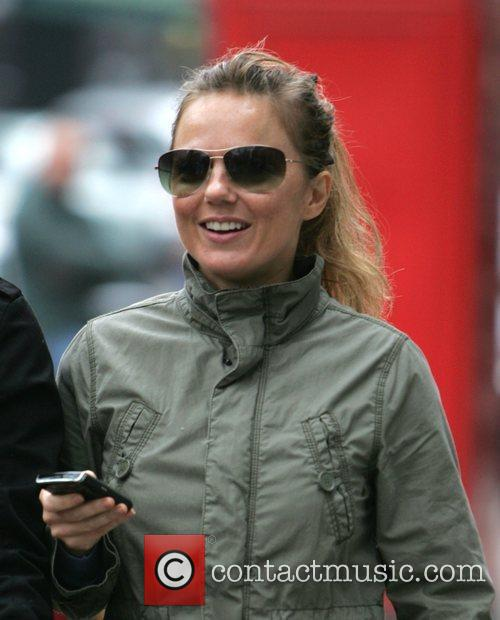 Geri Halliwell smiling and using a mobile device...