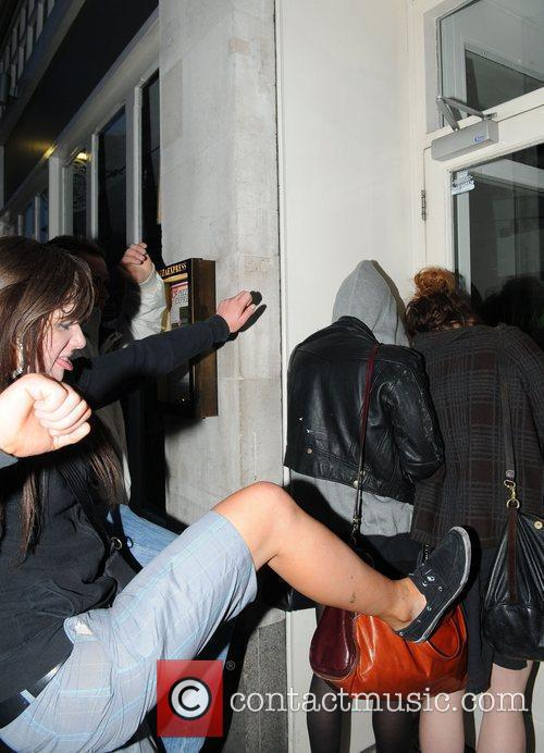 Pixie Geldof, a friend are huddled in a corner while a drunk passer by hurles abuse and attempts to kick the pair. Pixie was leaving Groucho Club after a night out with friends. 5