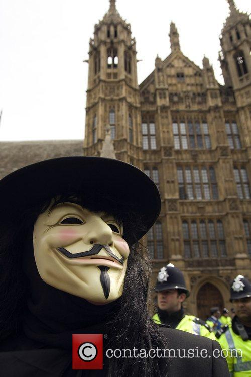A demonstrator dresses up as Guy Fawkes outside...