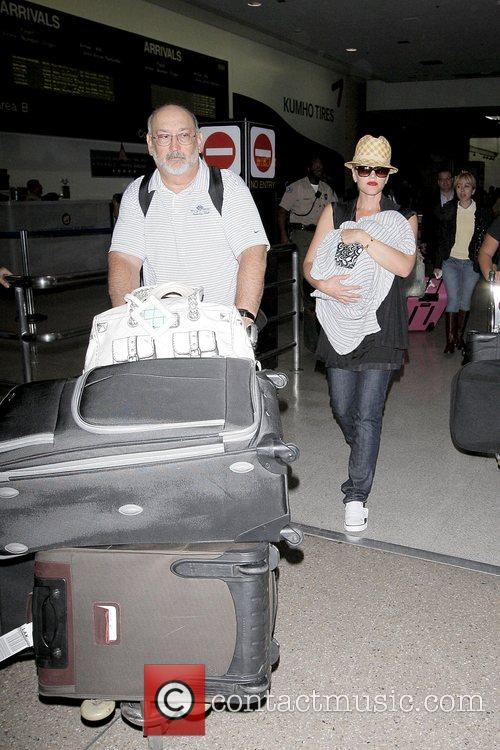 Gwen Stefani arrives at LAX while holding her...