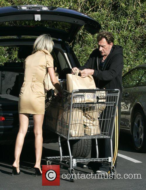 Johnny Hallyday and his wife Laeticia walk back...