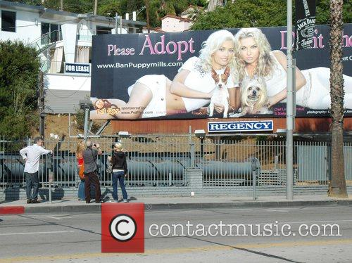 Holly Madison poses in front of a billboard...