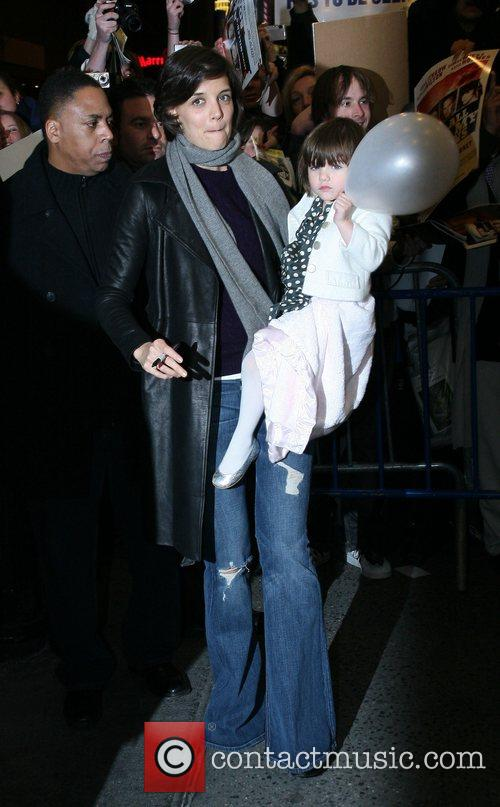 Katie Holmes carrys daughter Suri as they sign...