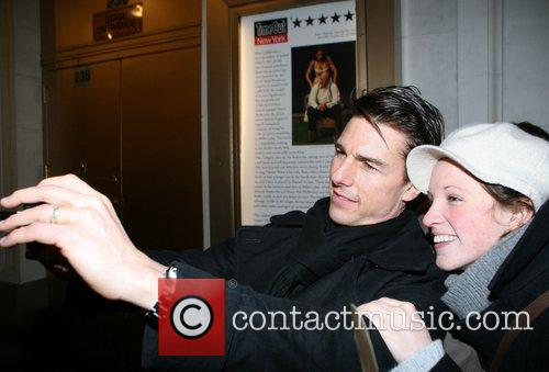 Tom Cruise poses for pictures with fans outside...