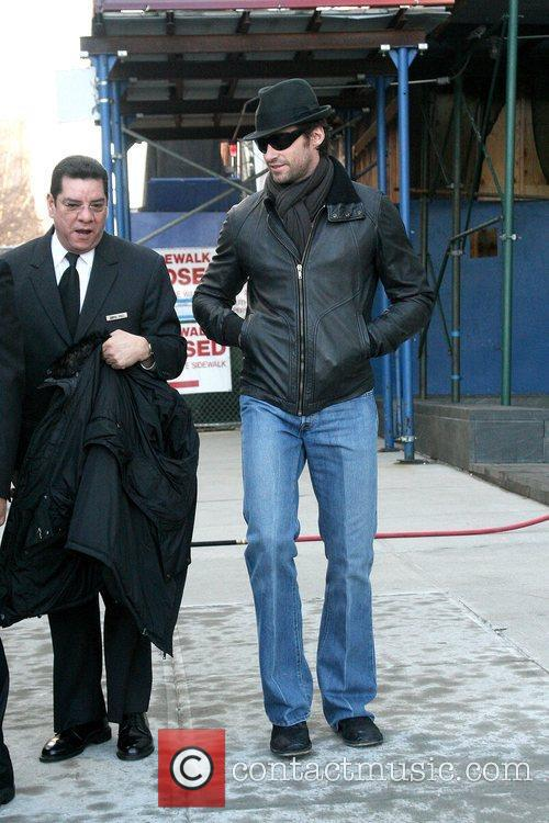 Leaving his Manhattan apartment with his wife while...
