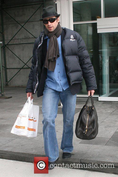 Hugh Jackman, wearing a fedora and dark sunglasses,...