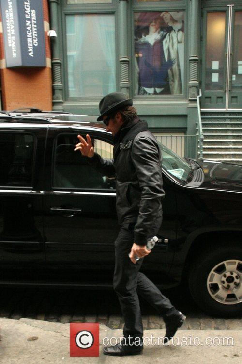 Hugh Jackman wearing all black, waves to the...