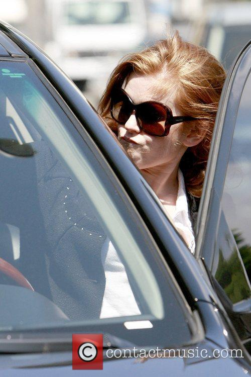 Isla Fisher walks to her car while out...
