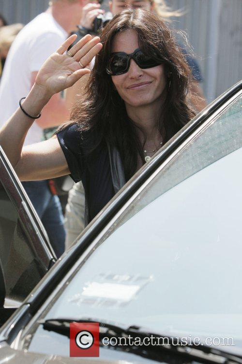 Courteney Cox  waves to photographers while leaving...
