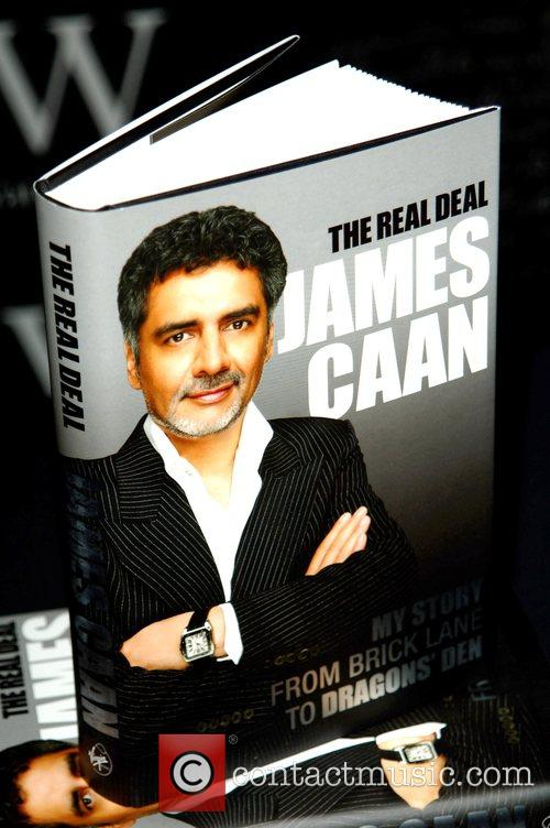 Signs copies of his book 'The Real Deal'...