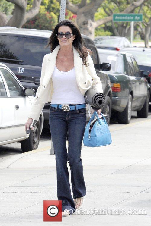Janice Dickinson carrying a yoga mat and bag...