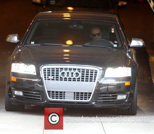 Jason Statham drivnig away after leaving a medical...