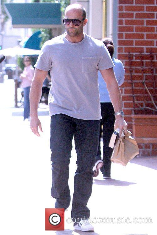 Jason Statham carrying a large paper bag while...
