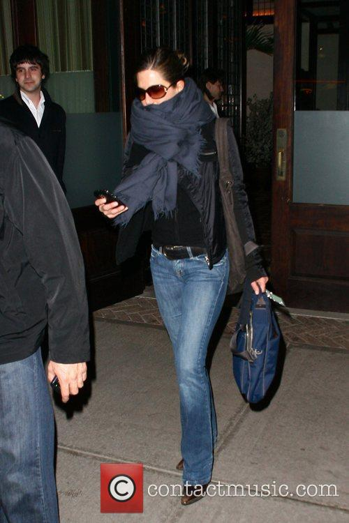 Jennifer Aniston shields her face from a cold...