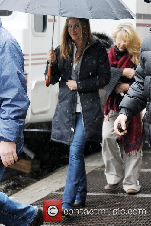Jennifer Aniston carrying an umbrella to shelter her...