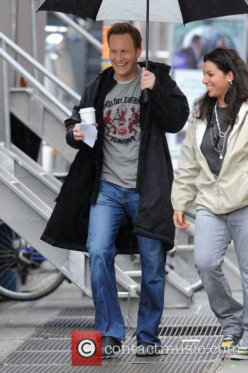 Patrick Wilson carrying an umbrella to shelter him...