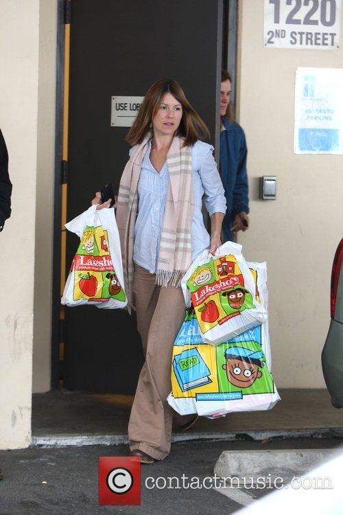 Jennifer Garner's assistant carries shopping bags as they...