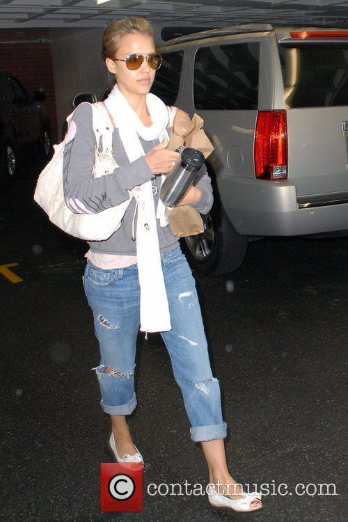 Jessica Alba, wearing ripped jeans and sunglasses, has...