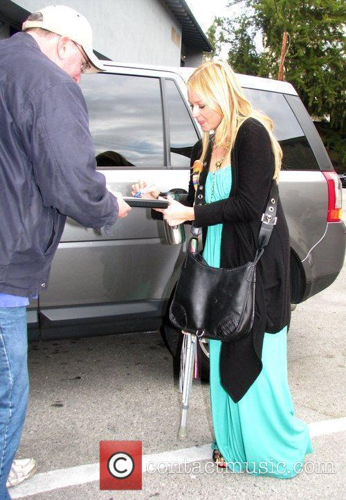 Jewel signs for a fan as she arrives...