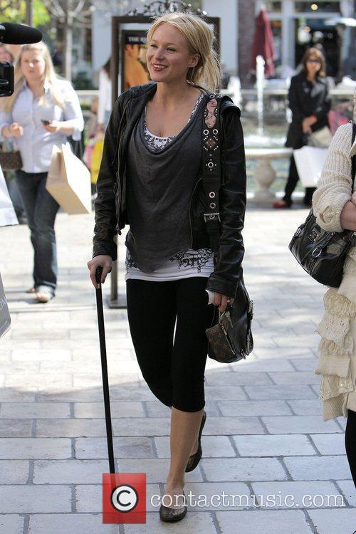 Jewel Kilcher walking with a cane while out...