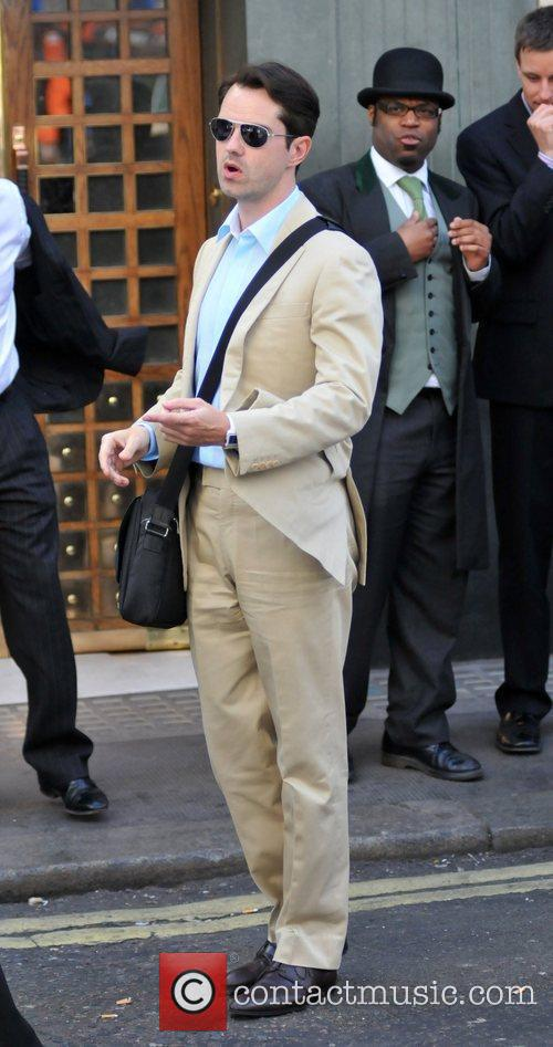Leaving the Ivy Restaurant, wearing a beige suit
