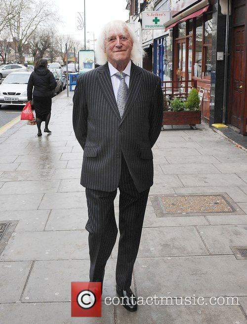 Sir Jimmy Savile walks in a suit in...