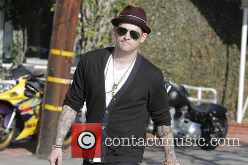 Joel Madden carrying a large shopping bag as...