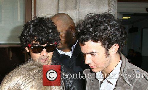 Joe Jonas and Kevin Jonas are surrounded by...